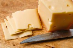 Stücke Käse auf hölzernem Schneidebrett und Messer Lizenzfreie Stockfotos
