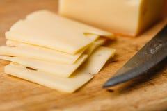 Stücke Käse auf hölzernem Schneidebrett und Messer Lizenzfreies Stockbild
