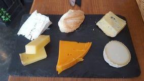 Stücke Käse auf woodenplatter Stockbild