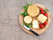 Stücke Käse auf woodenplatter Handwerkerkäse und -tomaten, auf grobem Sackzeug, Leinwand Stockfotos