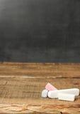Stücke Kreide auf einem hölzernen Hintergrund und einer Tafel Lizenzfreies Stockbild