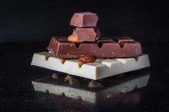 Stücke Milchschokolade mit Mandeln und Fliesen der weißen Schokolade mit Haselnüssen auf einem dunklen alten glatten Hintergrund Stockbild