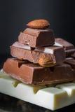 Stücke Milchschokolade mit Mandeln und Fliesen der weißen Schokolade mit Haselnüssen auf einem dunklen alten glatten Hintergrund Stockbilder