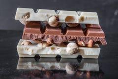 Stücke Milchschokolade mit Mandeln und Fliesen der weißen Schokolade mit Haselnüssen auf einem dunklen alten glatten Hintergrund Lizenzfreies Stockfoto