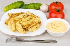 Stücke Ofenkartoffeln in der Platte, in den Gurken, in den Tomaten und im mayon Lizenzfreies Stockbild