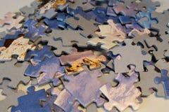 Stücke Puzzlespielblöcke auf Weißbuch mit Gebirgs- und Himmelmuster stockbilder
