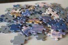 Stücke Puzzlespielblöcke auf Weißbuch mit Himmel- und Gebirgsmuster stockfotografie
