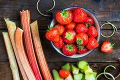 Stücke roher und frischer Schnitt-Rhabarber und Erdbeeren lizenzfreies stockfoto