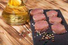 Stücke rohes Fleisch auf einer Platte von Schieferkrautgewürzen und von olivgrünem oi Lizenzfreie Stockfotos