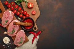 Stücke rohes Schweinefleischsteak auf Schneidebrett mit Kirschtomaten-, Rosmarin-, Knoblauch-, Pfeffer-, Salz- und Gewürzmörser a lizenzfreie stockbilder