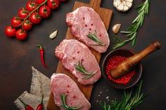 Stücke rohes Schweinefleischsteak auf Schneidebrett mit Kirschtomaten-, Rosmarin-, Knoblauch-, Pfeffer-, Salz- und Gewürzmörser a stockfoto