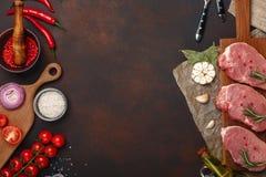 Stücke rohes Schweinefleischsteak auf Schneidebrett mit Kirschtomaten, Rosmarin, Knoblauch, roter Pfeffer, Lorbeerblatt, Zwiebel, stockfotografie