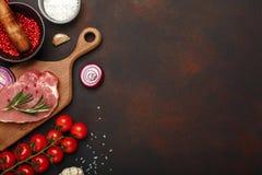 Stücke rohes Schweinefleischsteak auf Schneidebrett mit Mörser der Kirschtomaten, des Rosmarins, des Knoblauchs, des roten Pfeffe lizenzfreies stockfoto