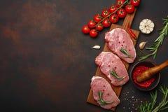 Stücke rohes Schweinefleischsteak mit Basilikum, Kirschtomaten, Rosmarin, Knoblauch, Pfeffer, Salz- und Gewürzmörser auf Schneide lizenzfreies stockfoto