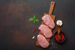 Stücke rohes Schweinefleischsteak mit Basilikum, Knoblauch, Pfeffer, Salz- und Gewürzmörser auf Schneidebrett und rostigem braune lizenzfreie stockfotos