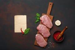 Stücke rohes Schweinefleischsteak mit Basilikum, Knoblauch, Pfeffer, Salz- und Gewürzmörser und Blatt Papier auf Schneidebrett un stockfotografie
