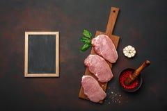 Stücke rohes Schweinefleischsteak mit Basilikum, Knoblauch, Pfeffer, Salz- und Gewürzmörser und Kreidebrett auf Schneidebrett und lizenzfreies stockbild