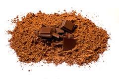 Stücke Schokolade im Kakaopulver Lizenzfreie Stockfotografie