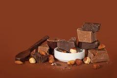 Stücke Schokolade mit Nüssen auf einem braunen Hintergrund Lizenzfreies Stockbild