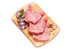 Stücke Schweinefleisch auf einem Schneidebrett stockfotos