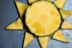 Stücke von Ananas in Form der Sonne auf einer Metalltabelle lizenzfreie stockfotografie