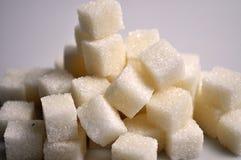 Stücke weißer quadratischer Zucker auf einem weißen Hintergrund lizenzfreie stockfotografie