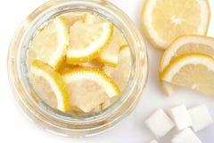 Stückschnitt der Zitrone in einer Glasschüssel und des Zuckers auf einem weißen Hintergrund Stockbilder