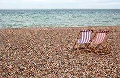 Stühle auf cobbled Strand Lizenzfreie Stockfotografie