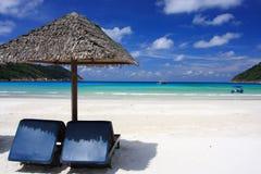 Stühle auf einem Inselstrand Stockbilder