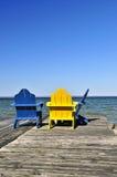 Stühle auf hölzernem Dock in See Stockfoto