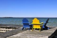 Stühle auf hölzernem Dock in See Lizenzfreie Stockfotos