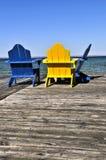 Stühle auf hölzernem Dock in See Stockbilder
