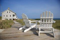 Stühle auf Plattform-Einfassung-Ozean Lizenzfreie Stockfotografie