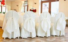 Stühle in den weißen Abdeckungen mit Bögen Dekoration von Stühlen für eine Gleichheit Lizenzfreies Stockfoto