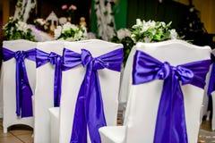 Stühle in den weißen Abdeckungen mit einem blauen Band Lizenzfreie Stockfotos