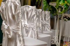 Stühle in den weißen Abdeckungen mit einem weißen Band Lizenzfreie Stockfotografie