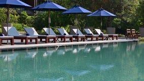 Stühle des Strandes 4K nahe Swimmingpool im tropischen Erholungsort stock video footage