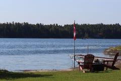 Stühle, die über schönem Seeblick mit Kanada-Flagge schauen lizenzfreies stockbild