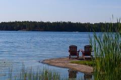 Stühle, die über schönem Seeblick schauen stockfotos