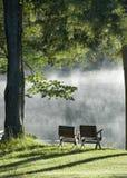 Stühle, die einen See übersehen Stockfotos