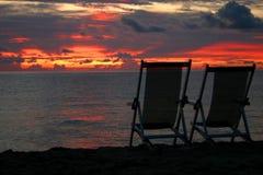 Stühle, die heraus auf Strandsonnenuntergang schauen Stockfotografie