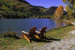 Stühle durch See Stockfotografie