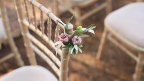 Stühle an einer Hochzeitszeremonie Verziert mit Blumenvorbereitungen stock video