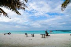 Stühle, Gazebo, Palmen und Sonnenschlechte auf dem Strand Stockfotografie