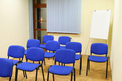 Stühle im classrom mit Tafel nach Lizenzfreie Stockfotos