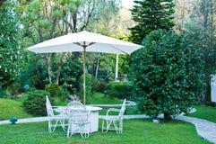 Stühle mit Regenschirm im Garten Stockfoto