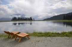 Stühle nähern sich einem See Stockfotografie