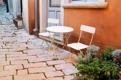 Stühle und eine Tabelle im Garten Stahlstühle und eine Tabelle, die in einem schönen Garten am sonnigen Tag steht Lizenzfreie Stockfotos
