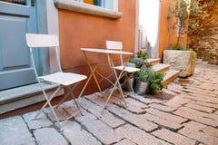 Stühle und eine Tabelle im Garten Stahlstühle und eine Tabelle, die in einem schönen Garten am sonnigen Tag steht Stockfotos