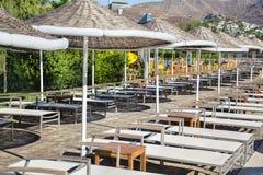 Stühle und mit Stroh gedeckte Regenschirme um einen Swimmingpool Stockbilder